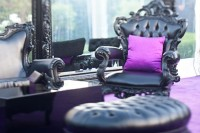 black gothic chair and ottoman with purple pillow